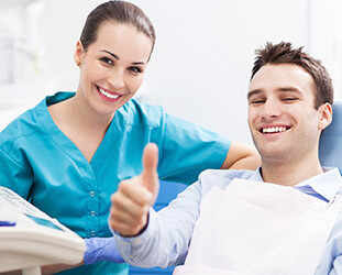 Man in dental chair gives thumbs up