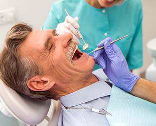 Older male patient laughing during dental examination