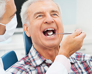 Older male patient examined in dental chair