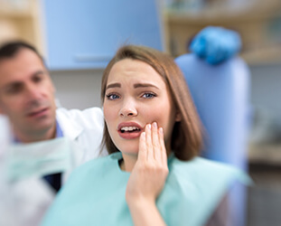 Upset woman holding cheek in dental chair