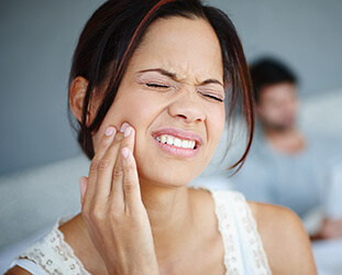 Woman grimacing in pain holds cheek